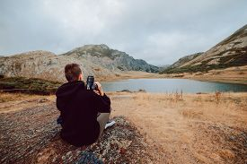Stock Photo Of A Photographer Girl Sitting In Front Of A Lake Surrounded By Mountains With A Camera