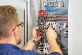 Electrician Man Measures Voltage With Multimeter In Electrical Cabinet. An Electrician Is Checking T