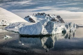 Iceberg and mountain backdrop near the Lemaire Channel along the Antarctic Peninsula.
