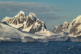Jagged mountains, glaciers and foreground icebergs along the Antarctic Peninsula.