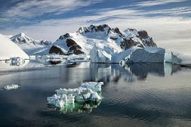 Iceberg in the waters of the Lemaire Channel with mountains and glaciers along the Antarctic Peninsula.