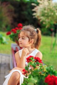 Beautiful Little Girl With  Flowers In Sunny Summer Park. Happy Cute Kid Having Fun Outdoors At Suns
