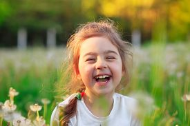 Beautiful Little Girl  Laughing And Playing With Flowers In Sunny Spring Park. Happy Cute Kid Having