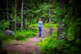 Woman On Curved Forest Road In Summer. Trees On Sides Of Road