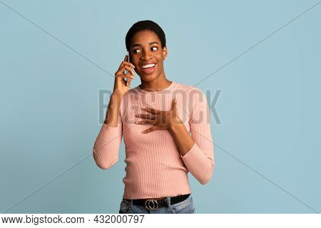 Unexpected Call. Surprised Young Black Woman Talking On Cellphone Over Blue Background