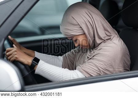 Upset Afro American Lady In Hijab Driving Car, Bowed Head And Regrets About Accident, Suffers From P