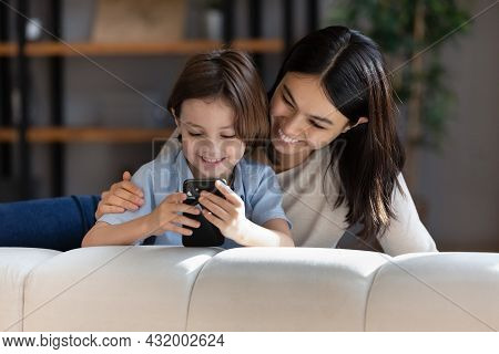 Affectionate Happy Young Asian Mother Using Cellphone With Small Kid.