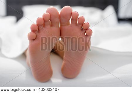 Girl Feet In A White Bed In The Morning. Enjoy And Relax In The Morning. Smooth Skin On The Heels.