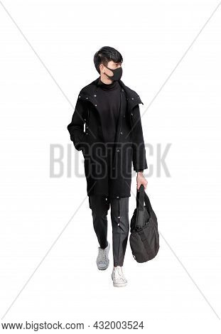 Young Handsome Man Wear Black Surgical Face Mask While Walking And Carry Bag Isolated On White Backg