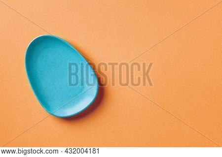 Blue Ceramic Oval Plate On An Orange Colored Background. Modern Ceramic Crockery, Serveware And Dinn