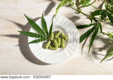 Cbd Oil Capsules In A Wooden Spoon And Fresh Green Cannabis Sativa Leaf Over White Wooden Table. Med