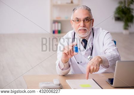 Old male doctor in vaccination concept