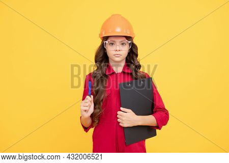 Serious Child Girl In Protective Hard Hat And Glasses Hold Folder With Paper Documents, Expert