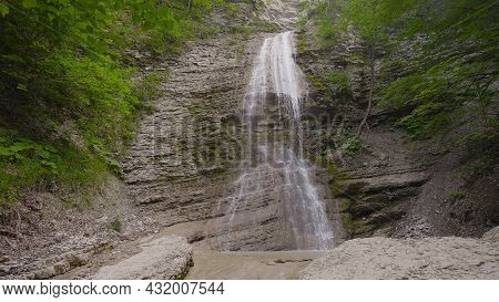 Small Beautiful Waterfall In Mountains. Action. Gentle Waterfall Flowing Down From Cliff Among Green