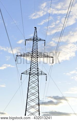 High-voltage Power Lines Are Very High In The Forest Against The Sky