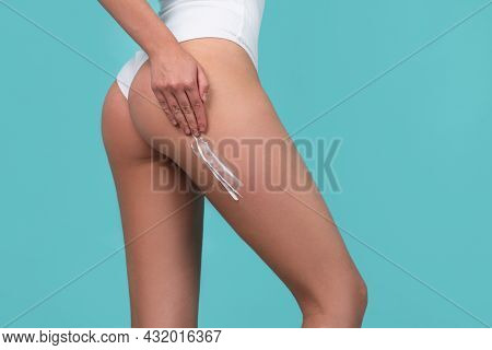 Body Care. Woman Applying Cream On Legs And Buttocks. Female Applying Cosmetic Cream From Cellulite.