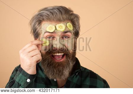 Funny Man With Clay Mask And Cucumber Slices On Face. Spa, Dermatology, Wellness And Facial Treatmen
