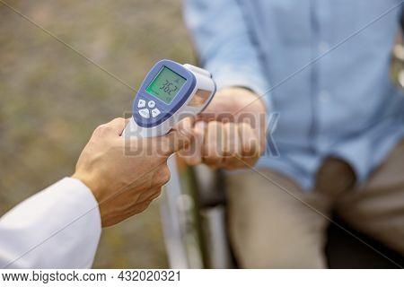 Close Up Shot Of Medical Infrared Thermometer In A Hand Of Doctor Measuring The Temperature Of Male