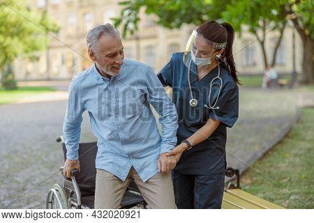 Supportive Nurse Wearing Face Shield And Mask Helping Mature Man, Recovering Patient In Wheelchair T