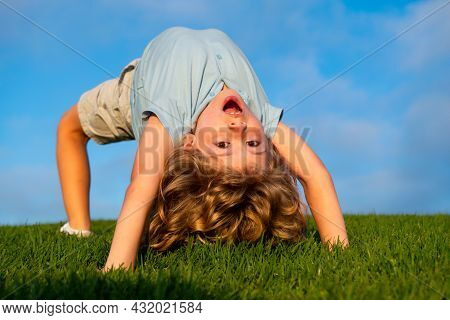 Happy Boy Doing A Headstand On The Grass In The Summer Sunshine. Funny Happy Little Child Standing O
