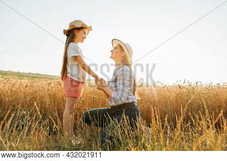Side View Of Mother And Daughter In Hat Holding Hands In Golden Wheat Field. Child And Woman Family