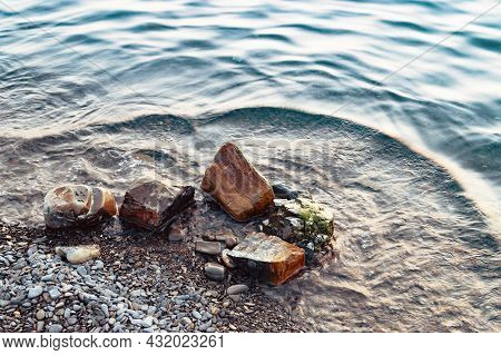 Boulders And Rocks On Sea Shore Washed With Waves And Causing Ripples On Water Surface