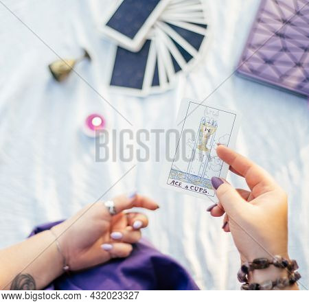 Female Hand With Purple Nails Holds Tarot Card Named Ace Of Cups Over White Surface With Notebook An