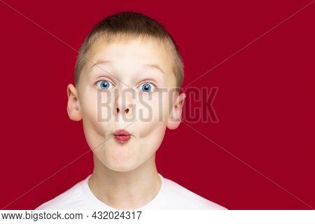 Boy Teenager 7-10 In A White T-shirt Makes Faces, Depicting A Kiss, With Wide Open Eyes On A Red Bac
