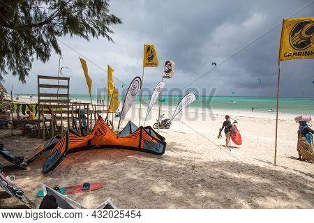 Zanzibar, Tanzania, January 22, 2021: Beach For Surfers, Turquoise Sea, A Girl With A Kite Goes Towa