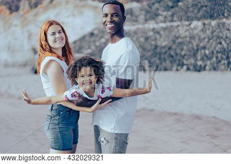 Happy Multiracial Family On The Beach. People Having Fun On Summer Vacation. Daughter Playing Like A