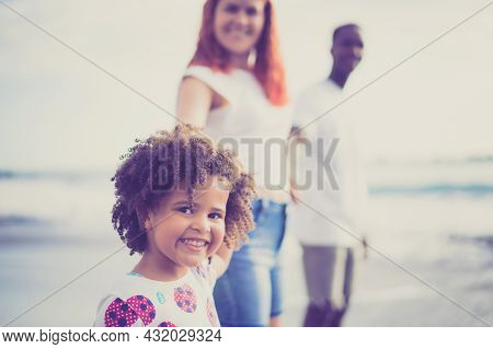 Little Girl Pulling Parents' Arms To Run To The Beach. Happy Multiracial Family Playing On The Beach