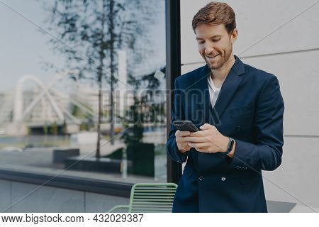 Pleased Handsome Male Ceo Or Director Holds Mobile Phone Waits For Call Scrolls Social Networks Whil
