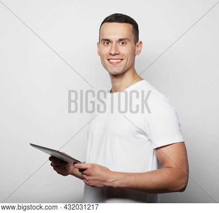 Tehnology and lifestyle concept: young man wearing white t-shirt using a tablet computer isolated over grey background