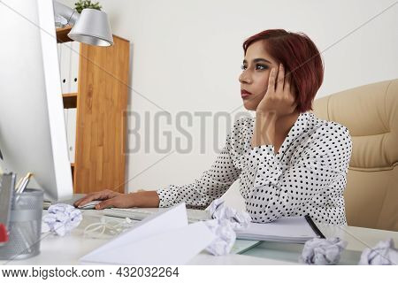 Tired Bored Female Office Worker Reading Article On Computer Screen Or Working On Report