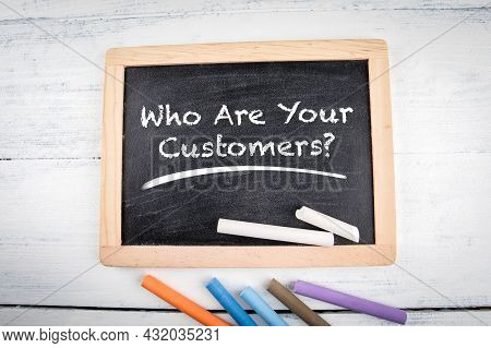 Who Are Your Customers. Chalk Board And Colored Chalk Pieces On A White Table