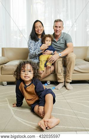Cute Positive Multi-ethnic Kid Sitting On He Floor, His Parents And Little Brother Sitting On Sofa I