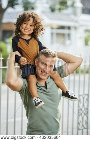 Portrait Of Happy Mature Man Giving Piggyback Ride To His Toddle Son When They Are Playing Outdoors
