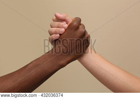 Men Clasping Hands On Beige Background, Closeup
