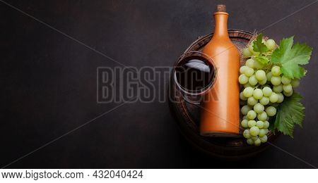 White grape, red wine glass and bottle on old wooden wine barrel. Top view flat lay with copy space