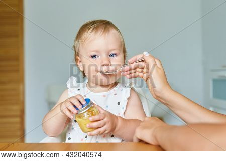 Faceless Mother Feeding Baby With Spoon. Child Sitting On High Chair While Mum Giving Food From Bott