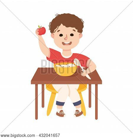 Little Boy At Kitchen Table Eating Porridge For Breakfast Engaged In Daily Activity And Everyday Rou