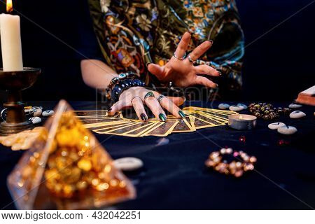 The Witch Spread Out Her Tarot Cards On The Table. Hands Close-up. The Concept Of Divination And Ast