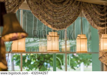 Pendant Lampshades In Shape Of Milk Cans Hanging By Window