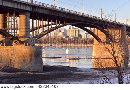 Arch Of The Oktyabrsky Automobile Bridge Over The Ob River. Powerful Pillars, Tall Houses On The Sho