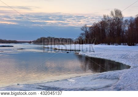 The Curved Bank Of The Ob River At Dawn, Snow And Ice On The Bank In Spring, Bare Trees On The Horiz