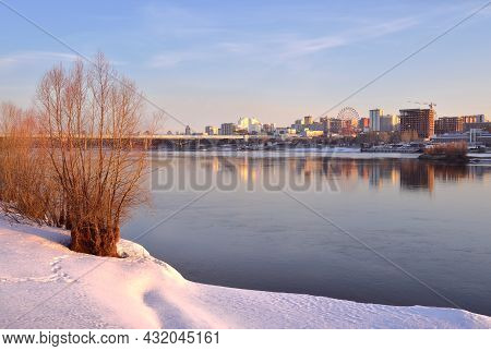The Ob River Bank In The Morning, Snow Bare Trees On The Bank In The Spring, Tall Houses And Bridges