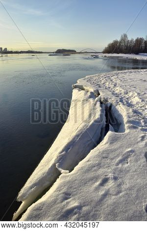 The Bank Of The Great Siberian River Is Covered With Snow And Ice, Early Spring. Arched Bridge And F