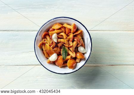 Pickled Mushrooms With Garlic And A Bay Leaf, Top Shot On A Rustic Wooden Background