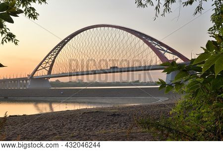 Bugrinskij Bridge Across The Ob River At Dawn. High Arched Cable Car Bridge Over A Wide River, Pink