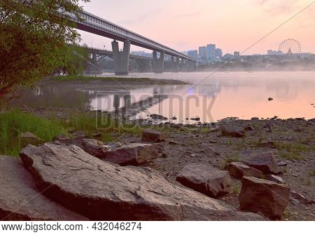 Rocky Shore Of The Ob In Novosibirsk. Big Stones On The Riverbank, Bridges, A Big City With A Ferris